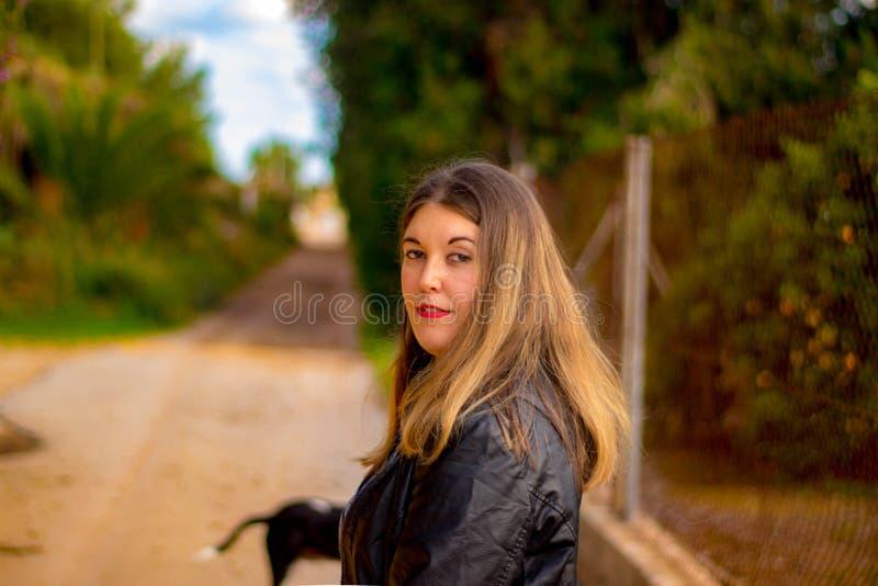 Modelo con la chaqueta negra en fondo exterior del bosque fotos de archivo