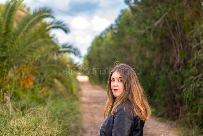 Modelo con la chaqueta negra en fondo exterior del bosque imagenes de archivo