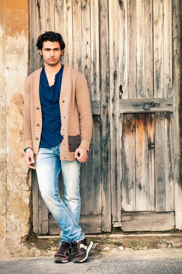 Modelo considerável italiano do homem perto de uma porta de madeira antiga foto de stock royalty free