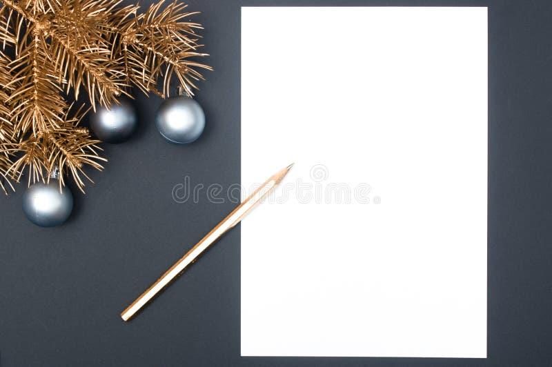 Modelo creativo de la decoración con las ramas de árbol de navidad de oro, las chucherías de plata y el lápiz con el espacio de l fotos de archivo
