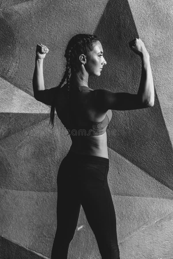 Modelo da aptidão que levanta mostrando os músculos da parte traseira e do bíceps imagens de stock royalty free