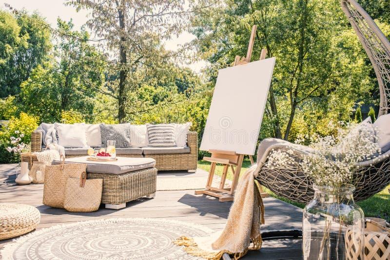 Modelo da armação no terraço no jardim com tabela e sofá do rattan durante o verão Foto real fotografia de stock