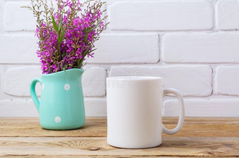 Modelo da caneca de café branco com as flores roxas marrons no passo da hortelã foto de stock royalty free