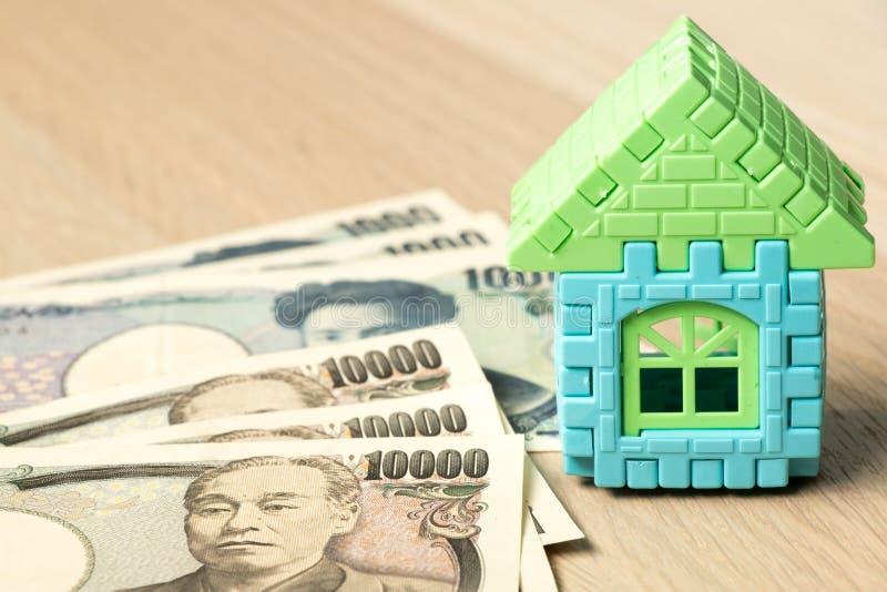 Modelo da casa com a cédula do iene japonês no fundo de madeira imagem de stock royalty free