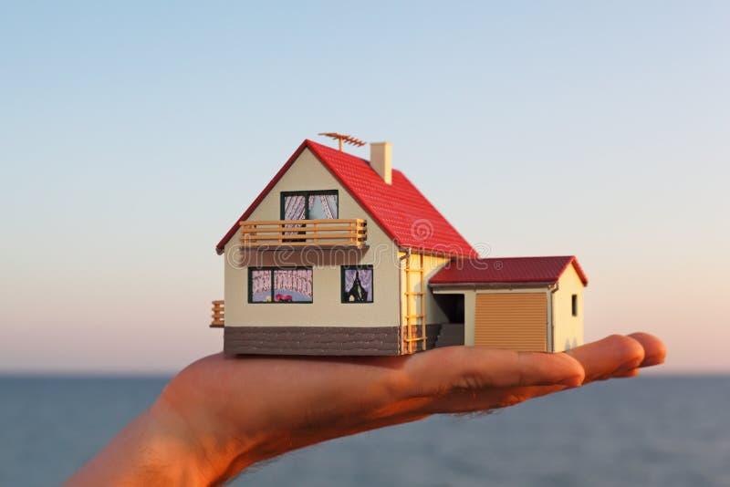 Modelo da casa com a garagem na mão de encontro ao mar imagem de stock royalty free
