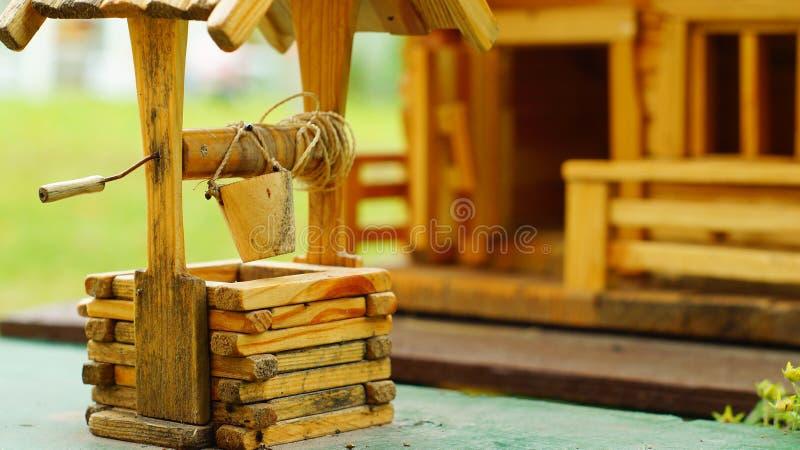 Modelo da casa de madeira com uma tração-bem imagens de stock