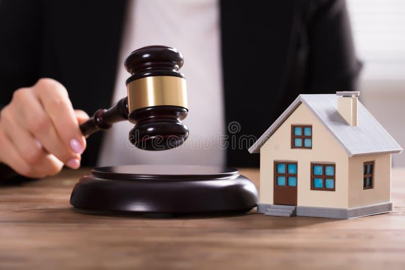 Modelo da casa de Striking Gavel Near do juiz imagem de stock