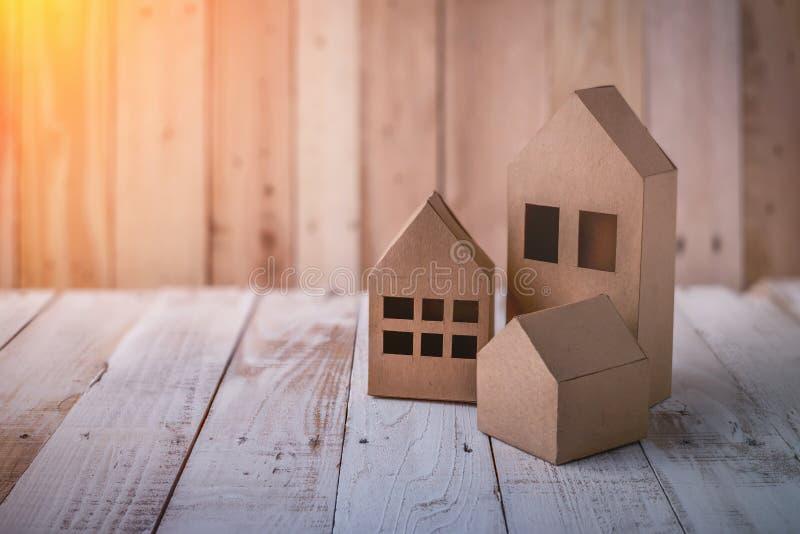 Modelo da casa do cartão no assoalho da grama verde e no backgroun cinzento imagem de stock royalty free