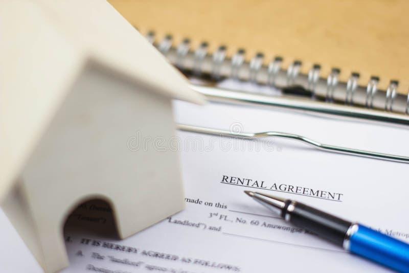 Modelo da casa e documento do acordo alugado com pena Descreve o processo do contrato de aluguer para a validez legal foto de stock