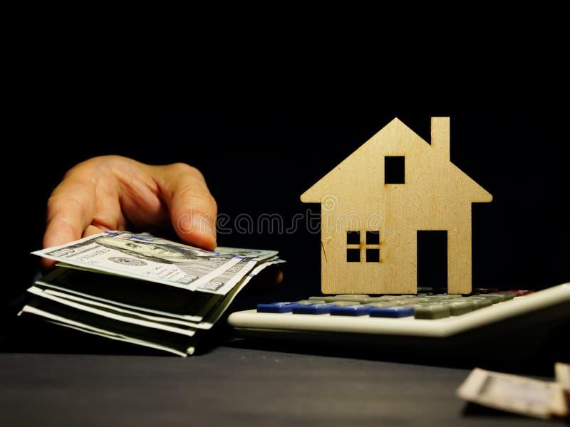 Modelo da casa e da mão com dinheiro Empréstimo comercial para bens imobiliários ou hipoteca fotografia de stock royalty free