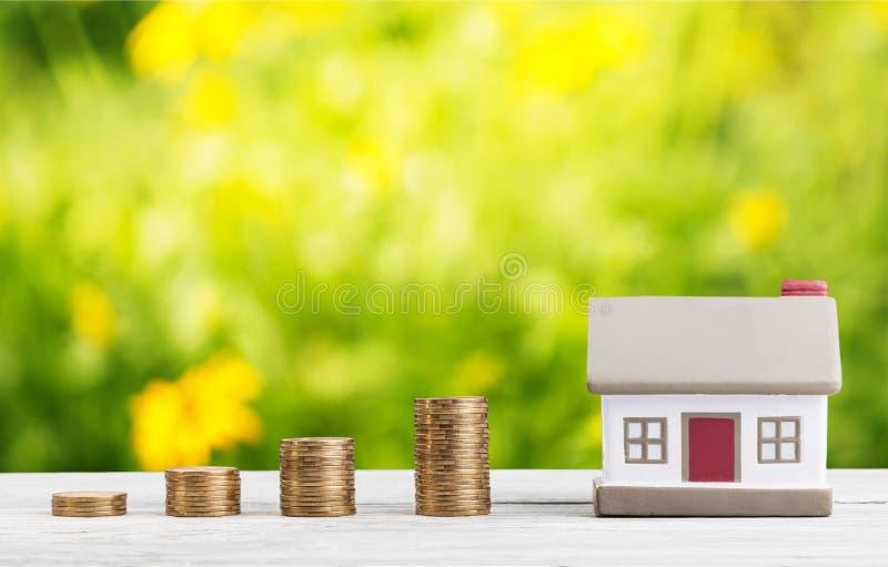 Modelo da casa e pilhas douradas das moedas imagem de stock