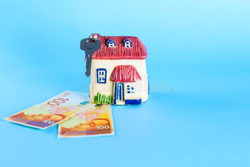 Modelo da casa e shekel novo de dinheiro-Israel do israelita no fundo azul foto de stock