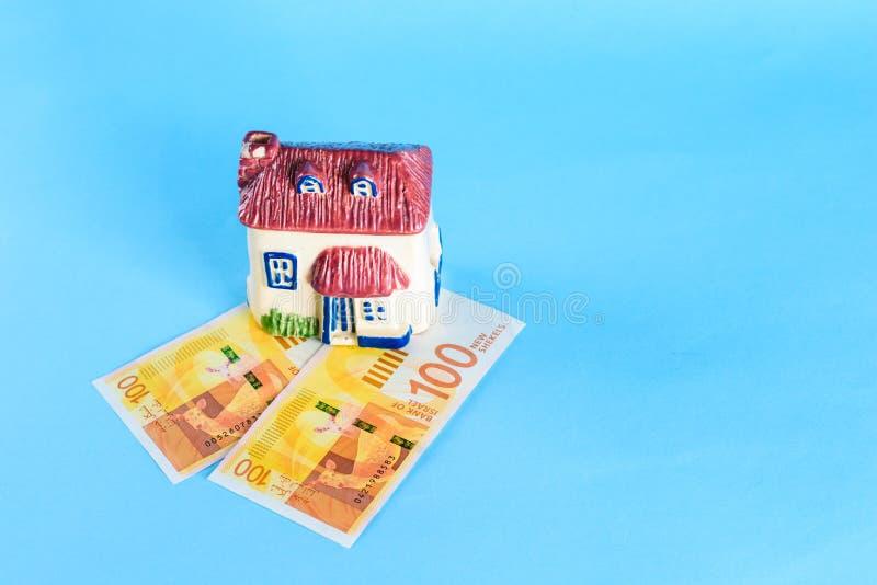 Modelo da casa e shekel novo de dinheiro-Israel do israelita no fundo azul fotografia de stock royalty free