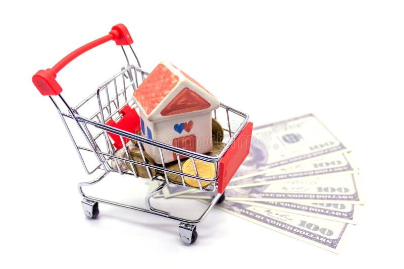 Modelo da casa no mini carrinho de compras com a pilha de dinheiro das moedas no blackground branco foto de stock royalty free