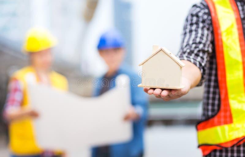 Modelo da casa ou da casa com os trabalhos de equipe do sucesso do engenheiro civil concentrados fotos de stock royalty free