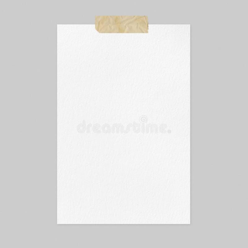 Modelo da folha do Livro Branco da placa com a fita adesiva em claro - fundo cinzento imagem de stock