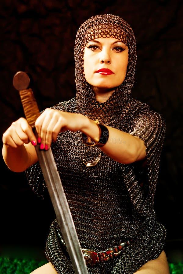 Modelo da jovem mulher na armadura de viquingue com espada imagem de stock