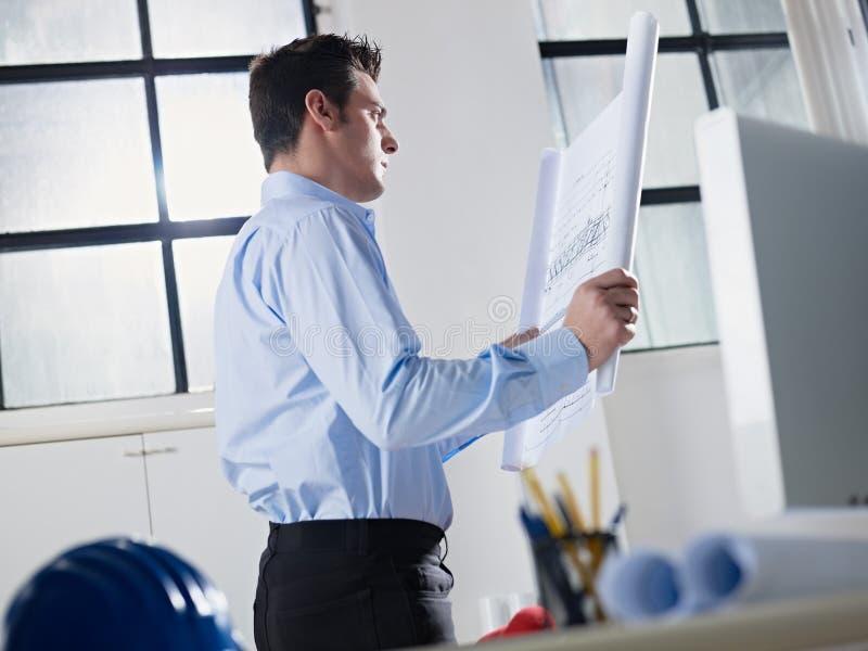 Modelo da leitura do arquiteto no escritório fotos de stock