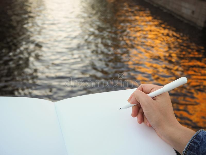 Modelo da mão da pessoa que guarda o caderno branco vazio que prepara-se para escrever para baixo o seu ou o seu ideias fotos de stock