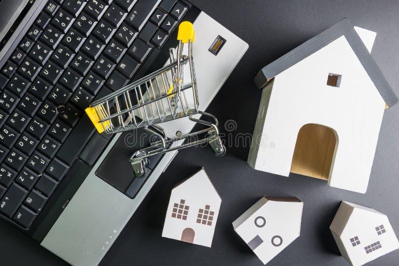 Modelo da mangueira do carrinho de compras e do papel no caderno do portátil Conceito em linha da compra Conceito dos bens imobil foto de stock
