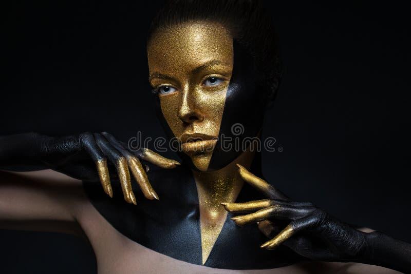 Modelo de alta moda con el cuero negro y del oro, fingeres de oro Aislado en cara femenina de la belleza negra del fondo, maquill foto de archivo libre de regalías