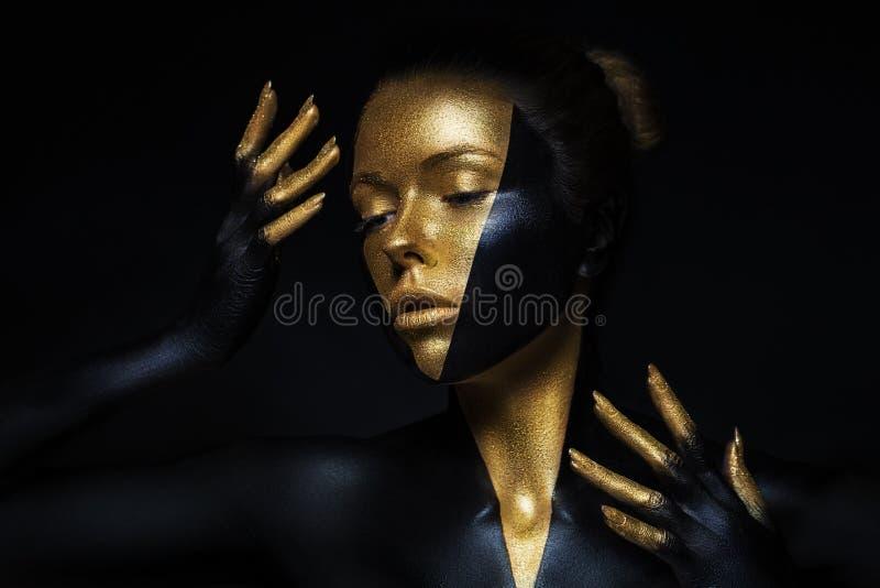 Modelo de alta moda con el cuero negro y del oro, fingeres de oro Aislado en cara femenina de la belleza negra del fondo, maquill imágenes de archivo libres de regalías