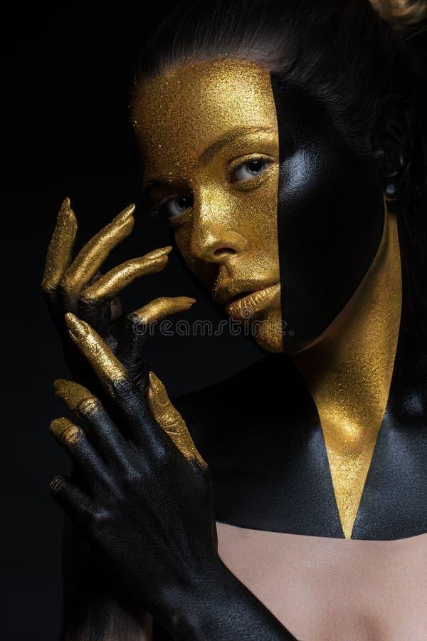 Modelo de alta moda con el cuero negro y del oro, fingeres de oro Aislado en fondo negro imagenes de archivo