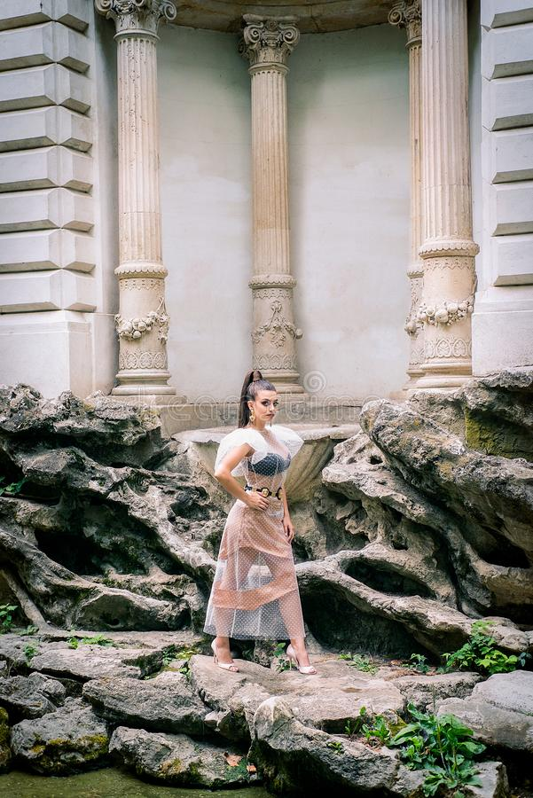 Modelo de alta moda con el vestido largo y la cola de caballo de Tulle que colocan u imágenes de archivo libres de regalías