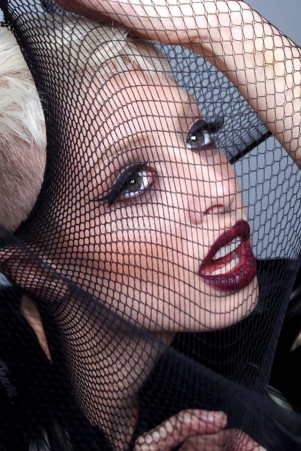 Modelo de alta moda Stretching Netting Over su cara imagen de archivo