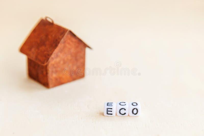 Modelo de brinquedo miniatura casa com letras ECO inscritas, palavra em pano de fundo de madeira Ecovillage, fundo ambiental abst fotografia de stock