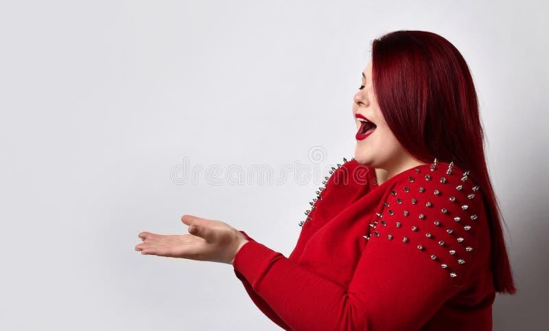 Modelo de cabeça-vermelha gordurosa em blusa vermelha-espiada Ela age como segurando algo, parecendo muito alegre, posando de lad foto de stock royalty free