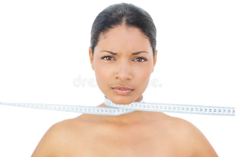 Modelo de cabelo preto alegre que estrangula-se com medição de Ta fotos de stock