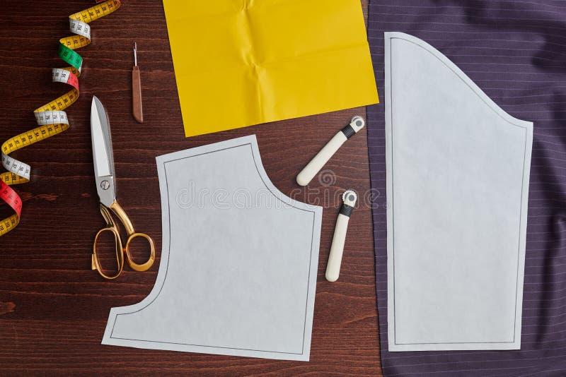 Modelo de costura en la tela, rueda de trazado, papel de trazo, equipo de costura fotos de archivo