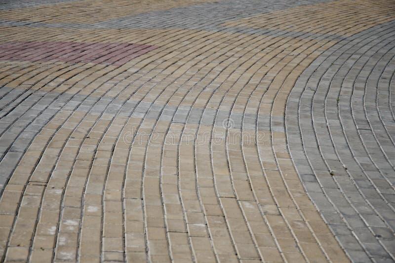 Modelo de diversas piedras de pavimentación de los colores que forman líneas redondeadas fotos de archivo