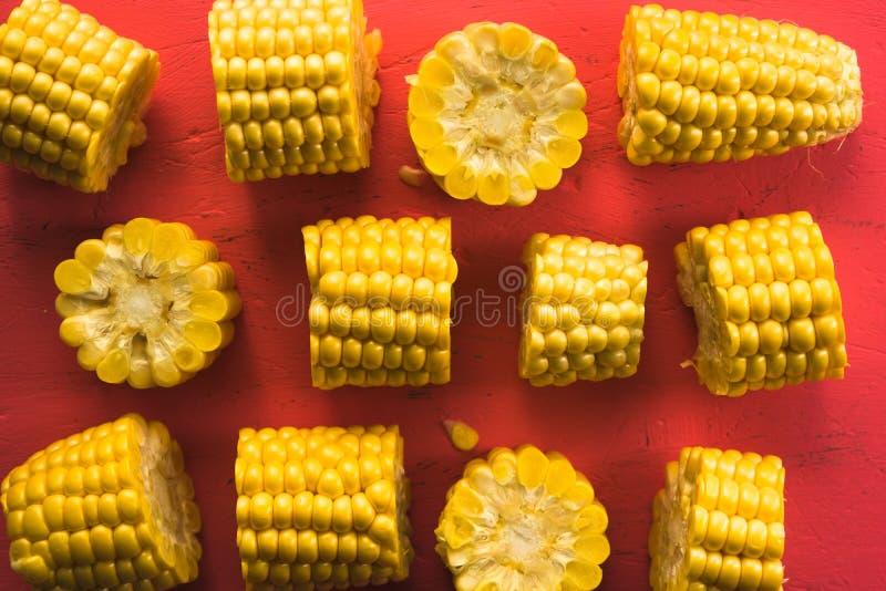 Modelo de diversos pedazos de maíz en una tabla rosada foto de archivo