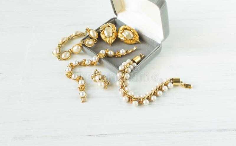 Modelo de fôrma Jewelry Fundo da joia do vintage Braceletes e brincos bonitos da pérola em uma caixa de presente na madeira branc imagens de stock
