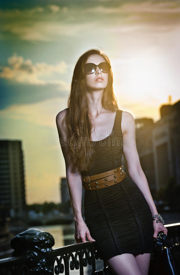 Modelo de fôrma na rua com óculos de sol e o vestido preto curto foto de stock