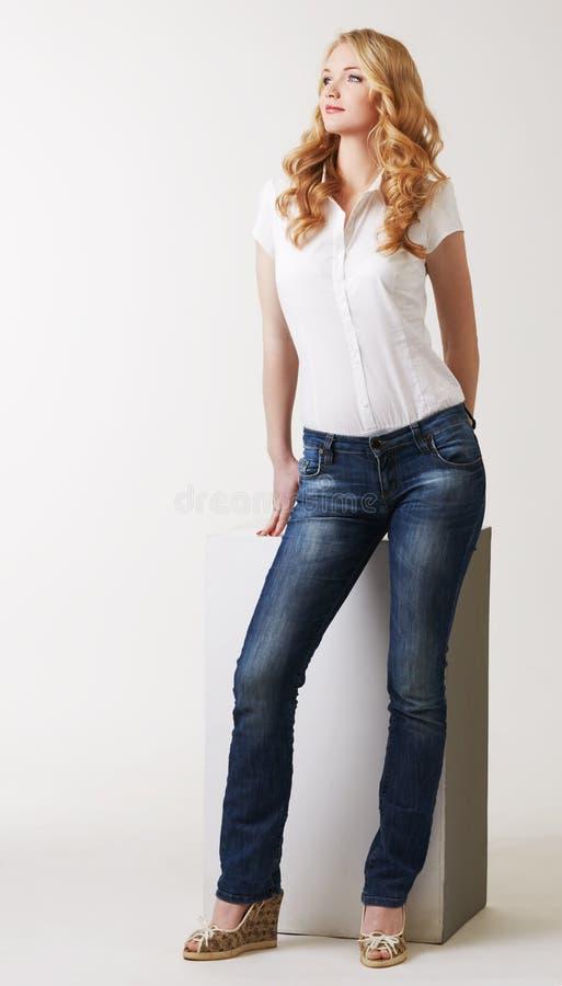 Modelo de fascínio que levanta na blusa e em calças de brim clássicas imagens de stock