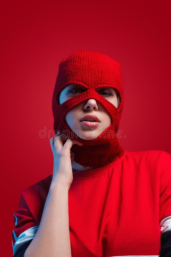 Modelo de fascinación en máscara hecha punto roja fotografía de archivo