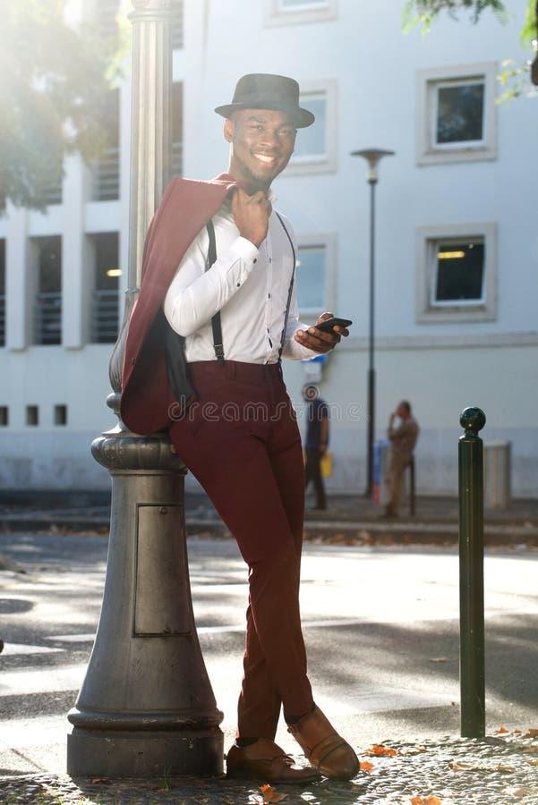 Modelo de forma afro-americano fresco do corpo completo com o terno do vintage que levanta com telefone celular na cidade fotografia de stock