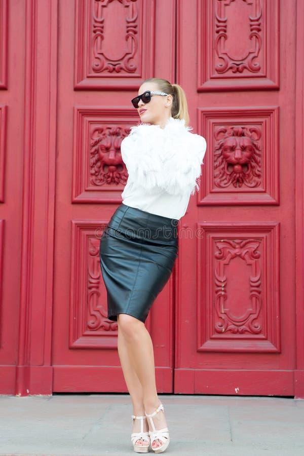 Modelo de forma com estilo da moda Mulher em sapatas do salto alto na porta vermelha em Paris, france Mulher 'sexy' nos óculos de fotografia de stock