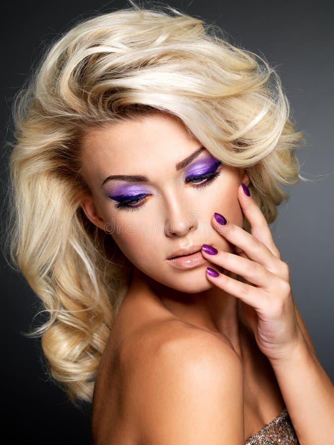 Modelo de forma com manicure e composição roxos fotografia de stock royalty free