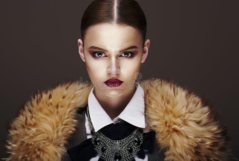 Modelo de forma restrito elegante bonito no casaco de pele. Luxo imagens de stock