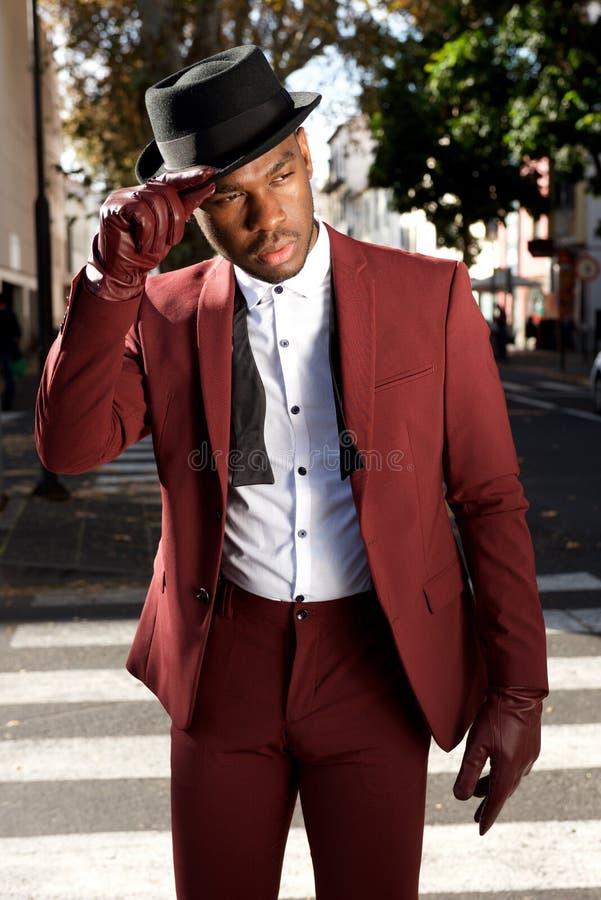 Modelo de forma masculino afro-americano fresco que levanta na rua da cidade com terno e chapéu do vintage fotos de stock