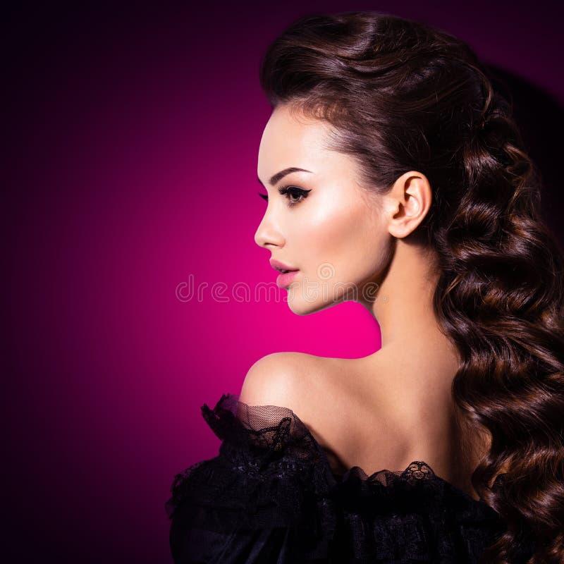 Modelo de forma no vestido dourado Modelo com um cabelo encaracolado longo Penteado criativo fotos de stock royalty free