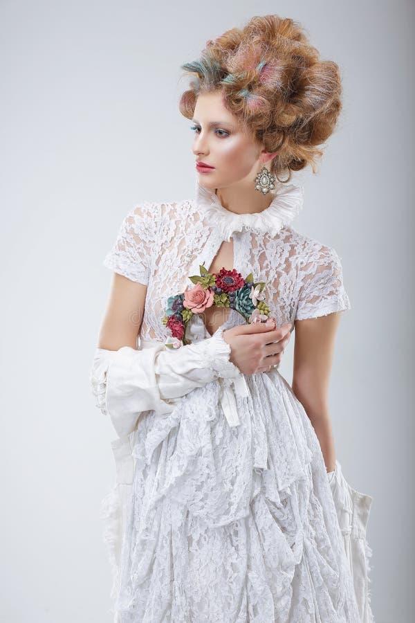 Modelo de forma no vestido e na grinalda brancos Flossy das flores fotografia de stock