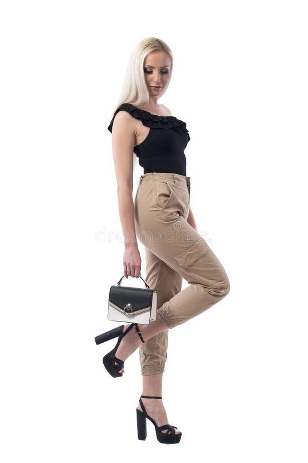 Modelo de forma novo à moda elegante que olha abaixo de guardar a bolsa pequena fotos de stock royalty free
