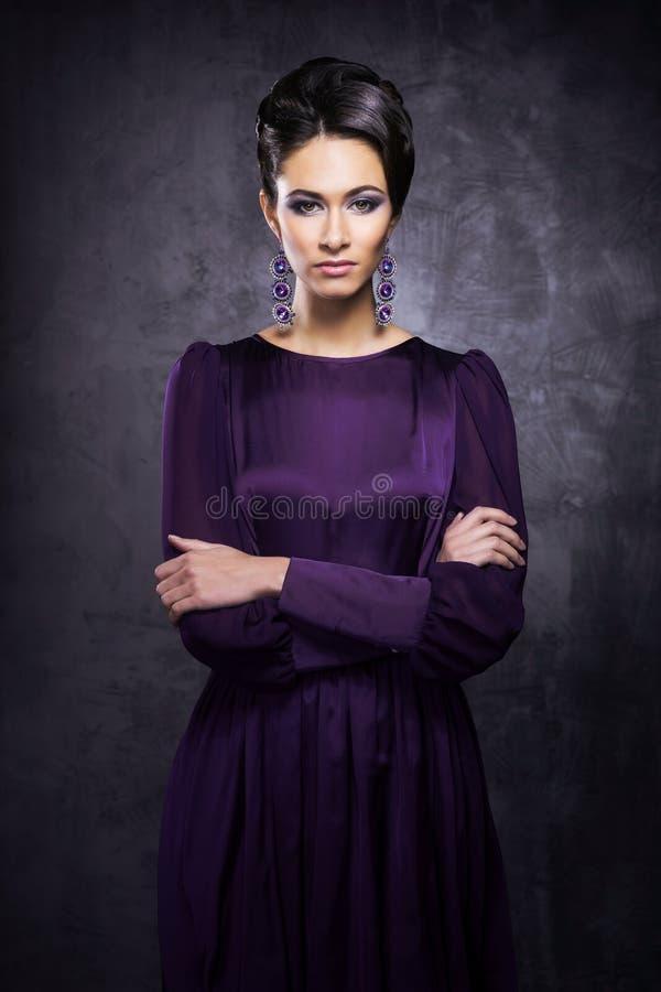 Modelo de forma novo e bonito que levanta em um vestido roxo imagens de stock