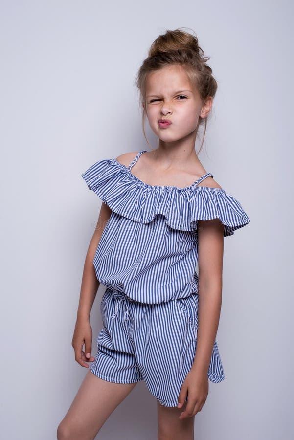 Modelo de forma pequeno bonito no fundo branco Retrato da menina de sorriso bonito que levanta no estúdio foto de stock