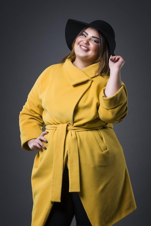 Modelo de forma positivo do tamanho no revestimento e no chapéu negro amarelos, mulher gorda no fundo cinzento, corpo fêmea exces foto de stock